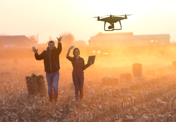 Happy farmers waving hands to drone