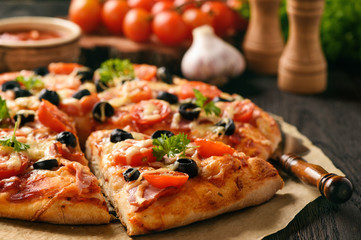 Homemade pizza with ham, cheese, tomatoes and olives.