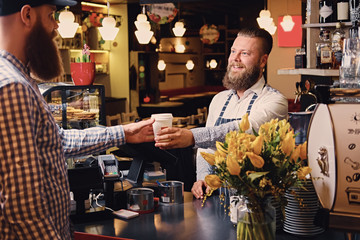 A man selling coffee to a consumer in a coffee shop.