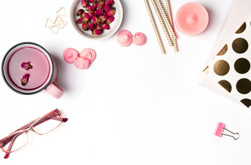 Pink and gold colored objects on the desk.
