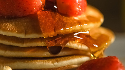 Close up of maple syrup oozing down stacked pancakes with strawberries