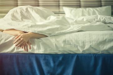 Female hands under blanket at sunset. Sleeping girl