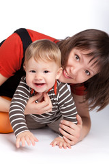 Mom teaches her six-month-old child in a striped blouse to smile at the camera. Pure white background