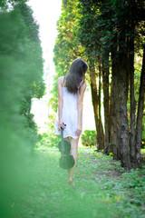 Девушка в коротком белом платье идет босиком со скрипкой по лесу