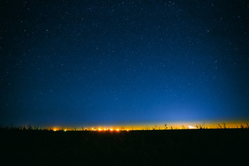Night Starry Sky Above Field And Yellow City Lights On Background
