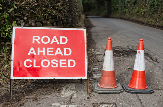 Road Ahead Closed sign and two traffic cones with country lane leading away to the background.