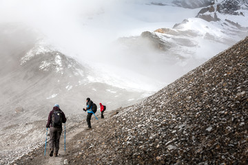 Trekker walking slowly to Thorung La pass - the highest point on Annapurna circuit in Nepal