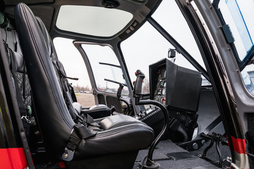 Helicopter cab interior, side view of the seat and the dashboard. Heli on the ground.