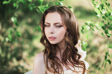 Beauty portrait of a very pretty young girl. Doll appearance. Woman with brown hair in a pink wedding dress on nature. Long hair. Natural light.