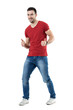 Cheerful excited young man in red t-shirt showing thumbs up gesture. Full body length portrait isolated over white studio background.