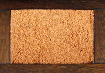 dried ground red pepper in wooden box isolated