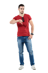 Upset angry young casual man showing thumbs down gesture. Full body length portrait isolated over white studio background.