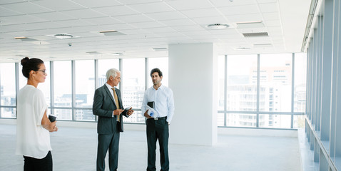 Real estate agent talking with clients inside an empty office sp