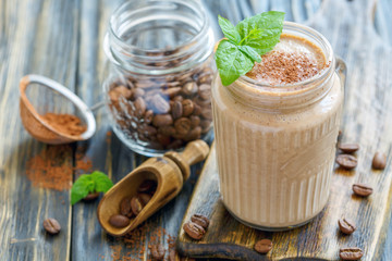 Coffee smoothie with banana in a glass jar.
