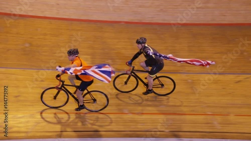 Cyclists on racing track in velodrome doing victory lap with flags