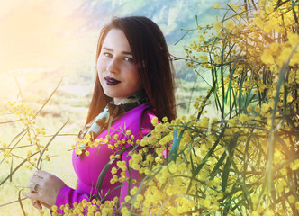 Young beautiful girl in a bright pink dress with a bouquet of yellow mimosa on nature. Portrait photography.