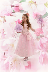 Young fairy in a pink dress and hairstyle with curls.