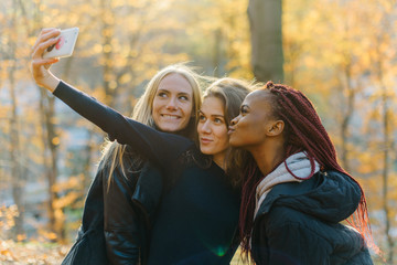Three Pretty female making selfie in autumn park. Cute girls with different colored skin. Female making funny faces and smiling at camera. Sunny autamn day
