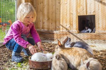 Mädchen im Stall mit Hasen