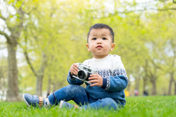 Asian baby with a camera in the park, London