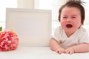 Crying baby boy with photo frame and flower