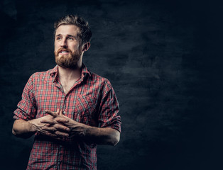 Studio portrait of blond bearded male over dark grey background.