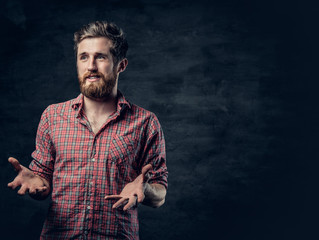 A positive bearded male dressed in a red fleece shirt tells a story with hand movement.