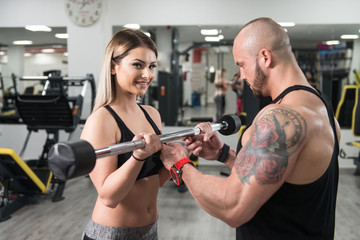 Woman Exercising Biceps With Her Personal Trainer