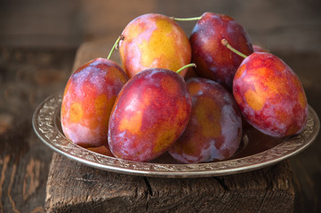 Heap of fresh ripe honeyed plums in old metal vintage plate on a wooden background, Rustic Style. Close up and copy space.