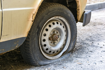 Flat tire of an old car on road