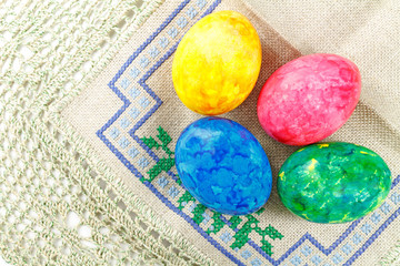 Colored Easter eggs on a coarse fabric with embroidery