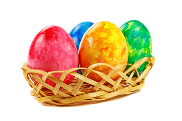 Colored Easter eggs in basket on white background