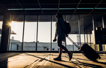 Fotobehang Luchthaven Silhouette of young girl walking with luggage walking at airport terminal window at sunrise time,travel concept,journey lifestyle