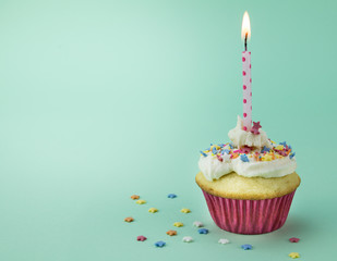 One cupcake with lit candle and star sprinkles isolated on green background