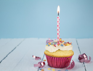 Cup cake with one candle on blue background with pink ribbons