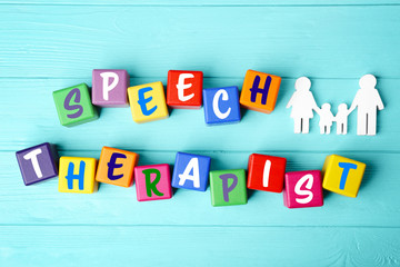 Speech therapy concept. Colourful cubes on blue wooden background