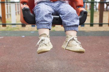 child sitting on swing in park