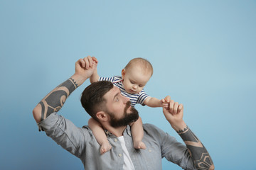 Handsome tattooed young man holding cute little baby on light background