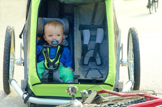 Cute baby sitting in child stroller. Bicycle trailer has two seats and is joined to bike on the road.
