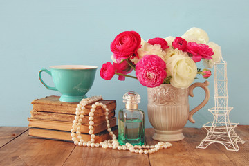 flowers in the vase next to old books, pearls necklace and perfume bottle
