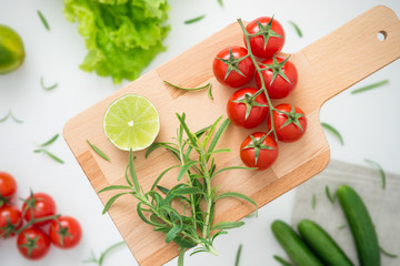 Raw ingredients for delicious salad on wooden board ready for cooking, with blurred background, top view