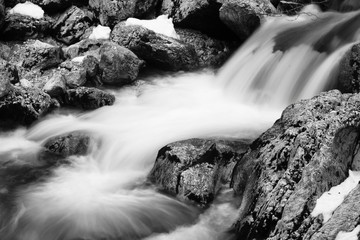 rocks in river brook in satin soft water flowing around in long exposure in black and white