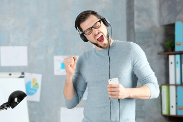 Handsome man listening to music at workplace
