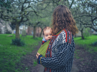 Woman with baby in carrier in the park