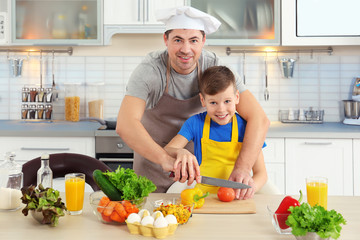 Father and son cooking together in kitchen