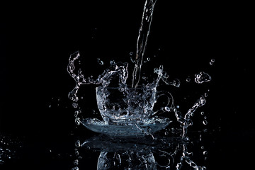 Water pours into a clear glass cup, black background, studio light