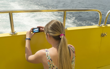 Woman taking a photo on a ship on the sea