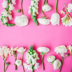 Pattern of white flowers - ranunculus, snapdragon, tulip and freesia on pink background. Flat lay, top view. Floral frame