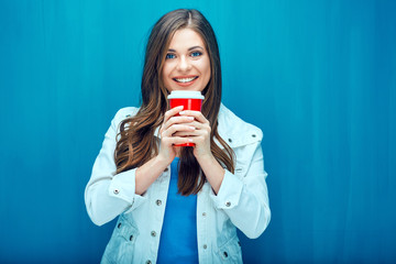 Young woman drinking coffee from red glass.