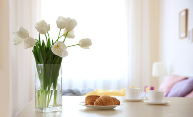 Vase with beautiful white tulips and plate with croissants on light table